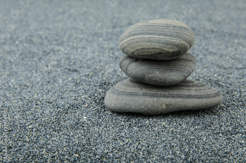 Poster de jardin Zen pierres a sable background of sea smooth stones. pyramid of stones on gray sand background with free space