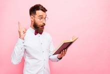 Photo Of Thoughtful Intellectual Person Holding Opened Paper Literature In Hands Pointing Fore-finger Up Isolated Pastel Background