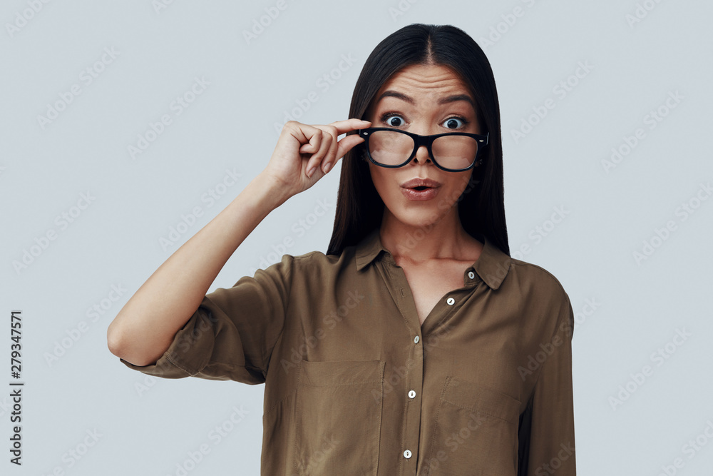Fototapety, obrazy: Acting silly. Attractive young Asian woman looking at camera and making a face while standing against grey background