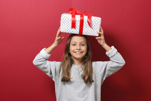 Cute Cheerful Girl In A Christmas Hat On A Colored Background Holding A Gift