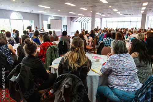 Atmosphere during corporate conference. A back view on a group of women sitting at a large table during a networking event for white collar workers. Lots of people can be seen watching a presentation