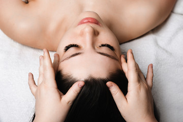 Close up portrait of a young attractive female having skin care facial massage by a cosmetologist in a wellness spa center.