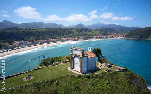 Chapel sits on top of a hill with beach and town on the background