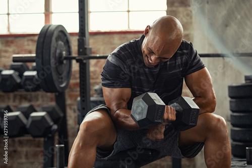 Fotografia Strong man lifting weight at gym
