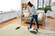 household, housework and cleaning concept - asian woman or housewife with vacuum cleaner at home