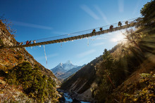Trekkers On Rope Hanging Suspension Bridge On The Way To Mount Everest Base Camp Near Namche Bazar - Nepal