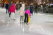 Group of people skating back to us. Family vacation with kid ice skating in city park, outdoor winter activity