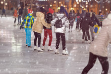Group Of Girls Skating Back To Us. Girlfriends Ice Skating In City Park, Snowy Evening. Healthy Outdoor Winter Activity