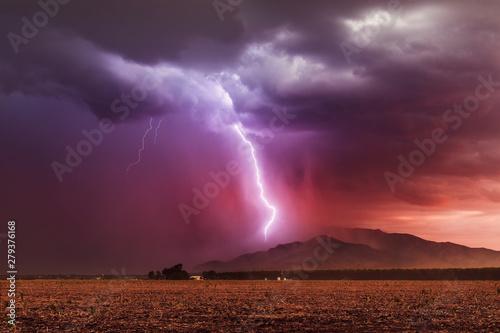 Foto auf AluDibond Aubergine lila Lightning bolt striking a mountain in a storm