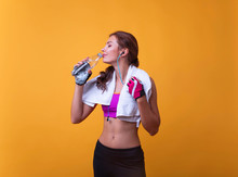 Image Of A Beautiful Strong Happy Cheerful Young Sports Woman Posing And Listening Music With Wireless Earphones Isolated Indoors Drinking Water With Towel On Neck.