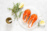 Fresh salmon steaks with ingredients for cooking on white board, view from above