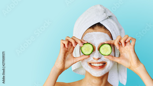 obraz dibond Beautiful young woman with facial mask on her face holding slices of cucumber. Skin care and treatment, spa, natural beauty and cosmetology concept.