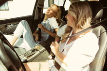 Young Lesbian's Couple Preparing For Vacation Trip On The Car In Sunny Day. Women Sitting And Ready For Going To Sea, Riverside Or Ocean. Concept Of Relationship, Love, Summer, Weekend, Honeymoon.