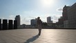 Young male skillfully riding skateboard pushing with foot on background of cityscape in sunlight. Handsome curly man skateboarding on windy sunny day while bright sun in blue sky illuminating city