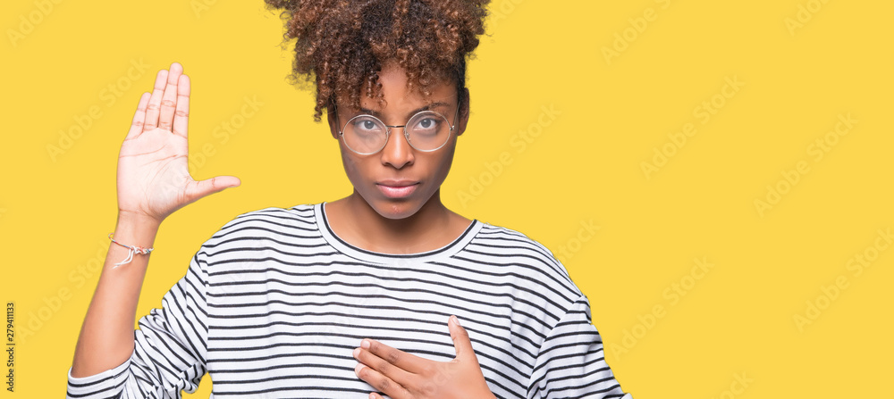 Fototapeta Beautiful young african american woman wearing glasses over isolated background Swearing with hand on chest and open palm, making a loyalty promise oath
