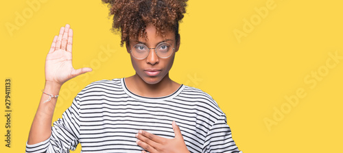 Obraz na plátne  Beautiful young african american woman wearing glasses over isolated background