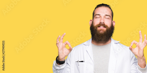 Valokuva  Young blond scientist man wearing white coat relax and smiling with eyes closed doing meditation gesture with fingers