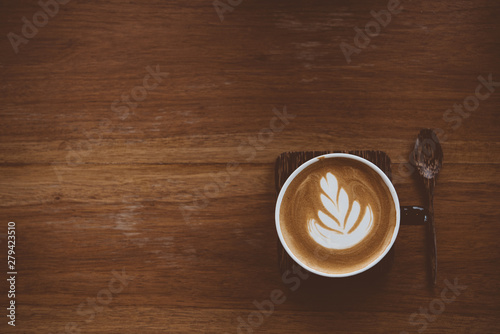 Photographie  Cup of coffee latte with beautiful latte art on wood table background,topview