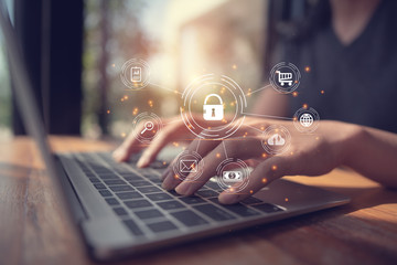 Business, technology, internet and networking concept.  businesswoman working on his laptop at home, select the icon security on the virtual screen.