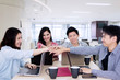Happy business team joining hands in the office