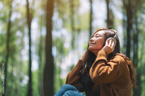 A beautiful asian woman enjoy listening to music with headphone with feeling happy and relaxed in the park - 279432780