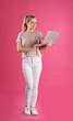 Leinwandbild Motiv Full length portrait of young woman with laptop on pink background