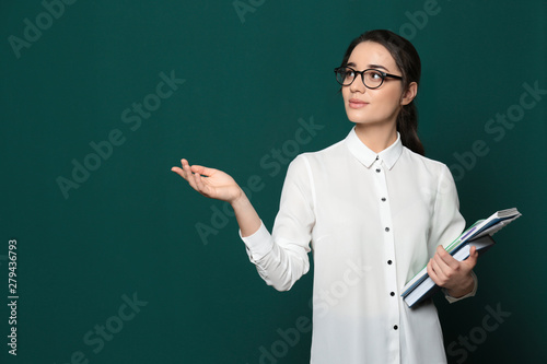 Portrait of beautiful young teacher with books near chalkboard, space for text Fototapeta