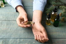 Woman Applying Essential Oil On Wrist At Wooden Table, Closeup
