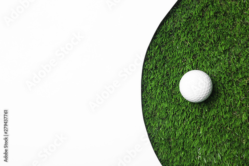 Fototapeta Golf ball and white paper on green artificial grass, top view with space for tex