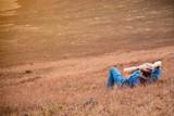 Fototapeta Sawanna - The man relaxing on outdoor. Lying down in sawanna area. Feeling relaxing.