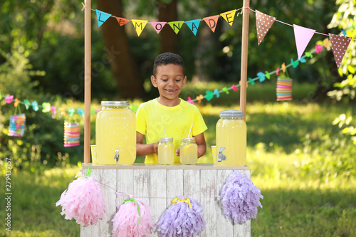 Fototapeta Cute little African-American boy at lemonade stand in park