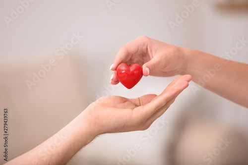 Obraz na plátně  Woman giving red heart to man on blurred background, closeup