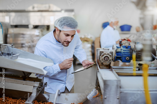 Young Caucasian serious supervisor evaluating quality of food in food plant while holding tablet Fototapete