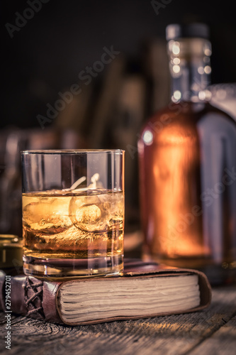 Tasty cognac with golden bottle and cold ice Canvas Print