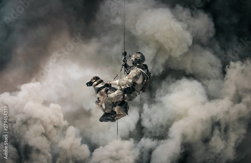 Military soldier with dog roping helicopter between mist and smoke Fototapet