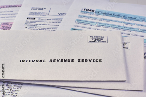 Three mails from the Internal Revenue Service lie on 1040