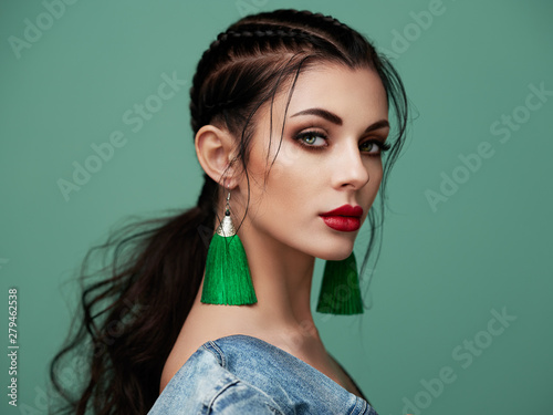 Obraz Brunette girl with perfect makeup. Beautiful model woman with curly hairstyle. Care and beauty hair products. Lady with braided hair. Model with jewelry. Turquoise background - fototapety do salonu