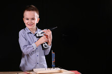 The Little Boy Is Holding A Screwdriver, Classes In The Carpentry Workshop. The Concept Of Teaching Child Labor In Schools. Hobbies And Creativity At School Age. The Concept Of Learning.