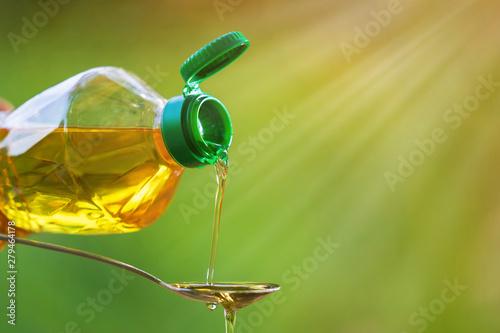 Fototapeta Hand pouring Vegetable oil from bottle to spoon obraz