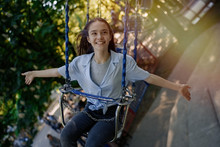 Happy Child Teenage Girl Riding Chain Carousel Swing At Amusement Park