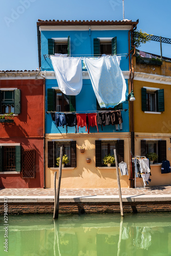 Cuadros en Lienzo Laundry dries on the facades of colorful houses with reflection in canal, Burano