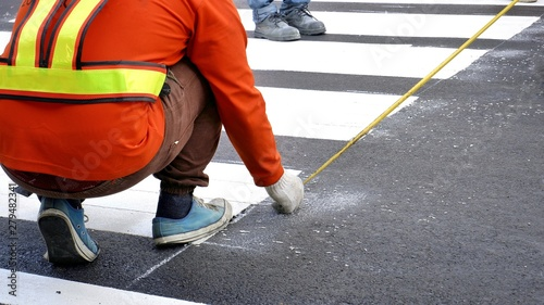 Photo Selective focus of road workers using measuring tape to make lines for pedestria