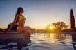 canvas print picture - Schöne Frau schaut sich den Sonnenuntergang am Swimming Pool an
