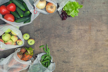 Fresh Organic Groceries In Reusable Recycled Mesh Produce Bags On Wooden Background With Copy Space. Zero Waste Shopping Concept. No Single-use Plastic.