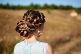 Fototapeta Kawa jest smaczna - Beautiful bride wedding hairstyle with jewelry, back view. Girl with curly hair styling outdoors. Hairdo for long hair with elegant accessories