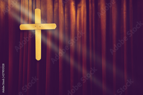 Obraz na plátně  yellow wood cross on dark brown curtain background in small church with ray of l
