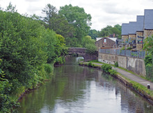A Stone Footbridge Crossing The Rochdale Canal In Mytholmroyd With Waterside Houses Surrounded By Trees