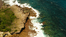 Ocean Waves Crashing On Rocky Shore From Above. Siargao, Philippines. Summer And Travel Vacation Concept