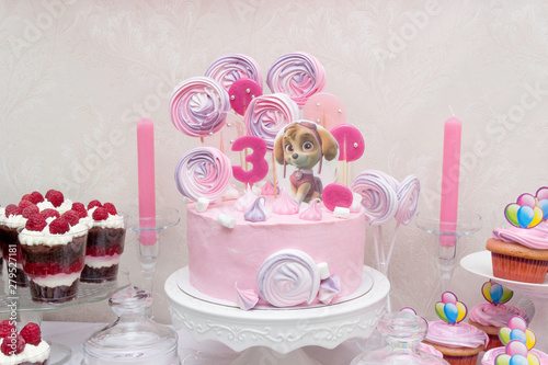 Photo  Сake with Paw Patrol character and cupcakes on the birthday of a little princess
