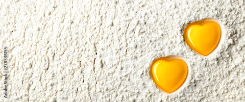 Fototapeta Two Yellow Heart Shaped Egg Yolks On White Flour Background - Love To Bake Conce
